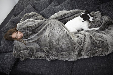 Young woman wrapped in fur blanket relaxing on couch with dog - RHF000733