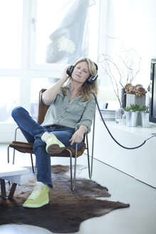 Woman hearing music with headphones at home - MAEF010043
