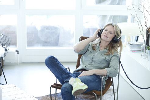 Woman hearing music with headphones at home - MAEF010044