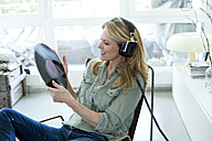 Woman holding record hearing music with headphones - MAEF010048