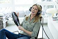 Woman holding record hearing music with headphones - MAEF010049
