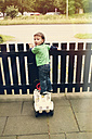 Boy, standing on toy car at a fence, looking over his shoulder, Erkrath, North Rhine-Westphalia, Germany - SBDF002776