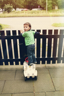 Boy, standing on toy car at a fence, looking over his shoulder, Erkrath, North Rhine-Westphalia, Germany - SBDF002776