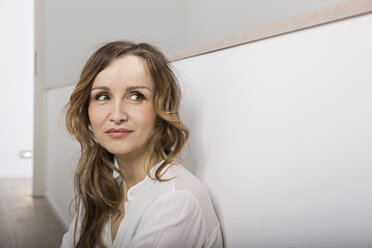 Portrait of smiling woman leaning against wall - PDF000906