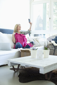 Woman sitting on couch taking selfie of her new clothing - MAEF010071