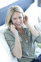 Portrait of smiling woman sitting on couch telephoning with smartphone - MAEF010073
