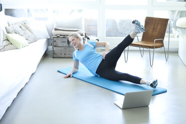 Woman with laptop exercising on gym mat in living room - MAEF010081