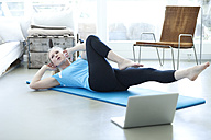 Woman with laptop exercising on gym mat in living room - MAEF010083
