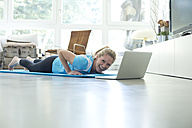 Woman with laptop exercising on gym mat in living room - MAEF010090