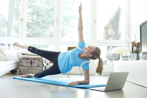 Woman with laptop exercising on gym mat in living room - MAEF010091