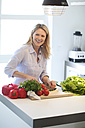 Smiling woman cooking in kitchen - MAEF010108