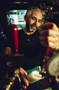 Man tapping beer in an Irish pub - MBEF001378