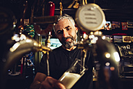Man tapping beer in an Irish pub - MBEF001393