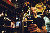 Man tapping beer in an Irish pub - MBEF001395