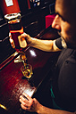 Waiter pouring whiskey in an Irish pub - MBEF001397