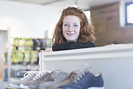 Portrait of smiling young woman in shoe shop - SGF001436