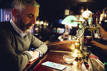 Man sitting at counter of a pub looking at his smartphone - MBEF001371