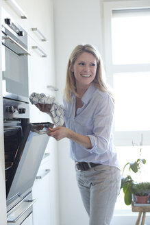 Smiling woman at oven in kitchen - MAEF010124