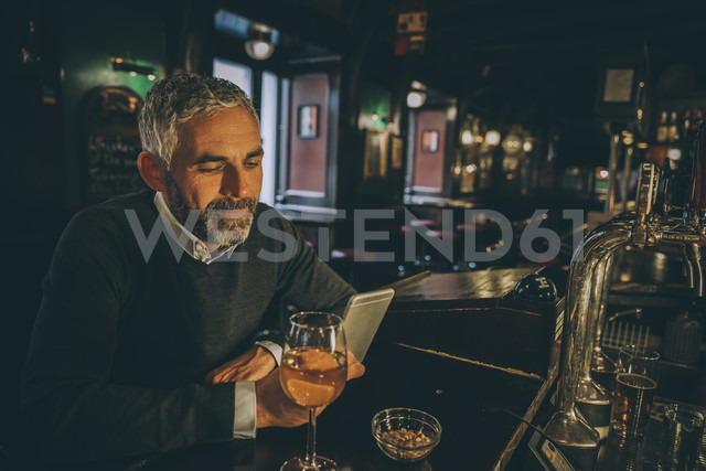 Portrait of man sitting at counter of a pub using smartphone - MBEF001358 - Martin Benik/Westend61