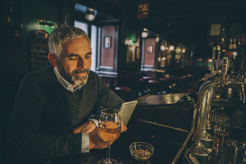 Portrait of man sitting at counter of a pub using smartphone - MBEF001358