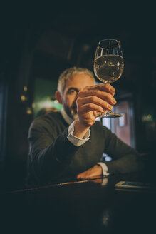 Man sitting at counter of a pub watching white wine glass - MBEF001360