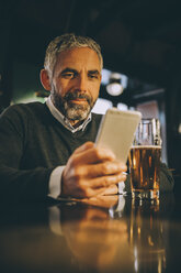 Man sitting at counter of a pub looking at his smartphone - MBEF001363