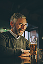 Smiling man sitting at counter of a pub with glass of beer - MBEF001367