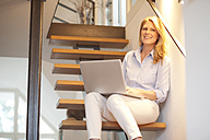Smiling woman using laptop on stairs - MAEF010132