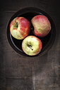 Bowl with three apples on dark wood - EVG001573