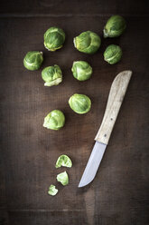 Brussels sprouts and a kitchen knife on dark wood - EVG001588