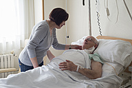 Senior woman caring for husband in hospital recovering after surgery - RAEF000108