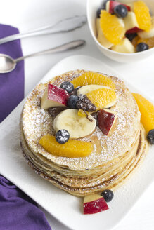 Stack of mini pancakes filled with chocolate cream and sliced fruits - YFF000349