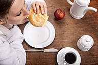 Woman in bathrobe having breakfast - MIDF000226
