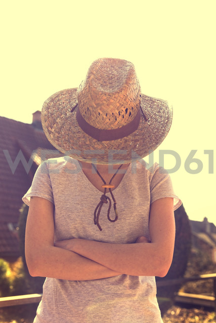 Woman with straw hat standing with arms folded - MIDF000253