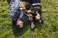 Couple lying with mongrel dog in meadow - MIDF000258