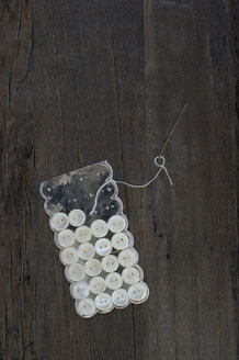 Cardboard of old mother-of-pearl buttons and sewing needle on dark wood - CRF002661