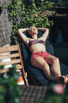 Young woman sunbathing on deck chair on her terrace - EBSF000468