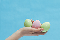 Woman's hand holding three coloured Easter eggs - BZF000088