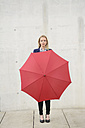 Businesswoman with red umbrella in front of concrete wall - BFRF001027