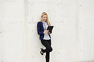 Smiling businesswoman with digital tablet leaning on concrete wall - BFRF001036