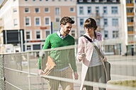 Young couple walking in the street, using mobile phone - UUF003793