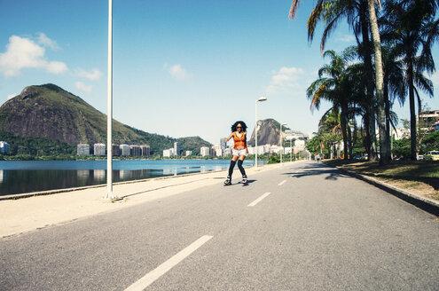 Brazil, Rio de Janeiro, female inline-skater on asphalt street - JUBF000010