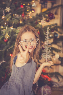 Portrait of happy little girl in front of Christmas tree - SARF001616