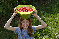 Portrait of smiling girl with bowl of raspberries on her head - LBF001109