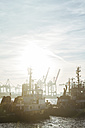 Germany, Hamburg, Port of Hamburg, Harbour cranes and towboats at sunset - KRPF001418