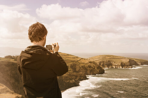 Portugal, Azores, man taking picture of coastal landscape - ONF000800