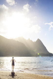 USA, Hawaii, Hanalei, woman standing on Haena Beach, View to Na Pali Coast in the evening light - BRF001116