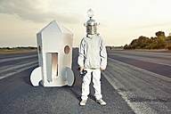 Boy dressed up as spaceman standing at cardboard rocket - EDF000144