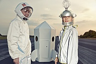 Two boys dressed up as spacemen standing at cardboard rocket - EDF000149