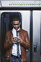 Spain, Barcelona, businessman with smartphone and earphones hearing music on the subway train - EBSF000483